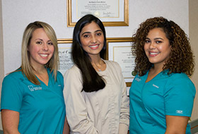 Dentist and team members smiling together