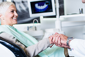 Older woman shaking hands with dentist