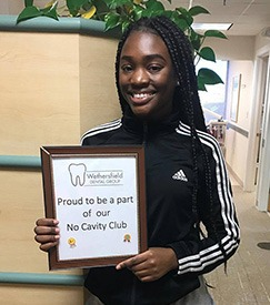 Young woman holding cavity-free club sign