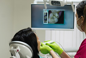 Dentist and team member looking at digital images