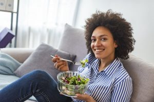 person on a couch eating a salad