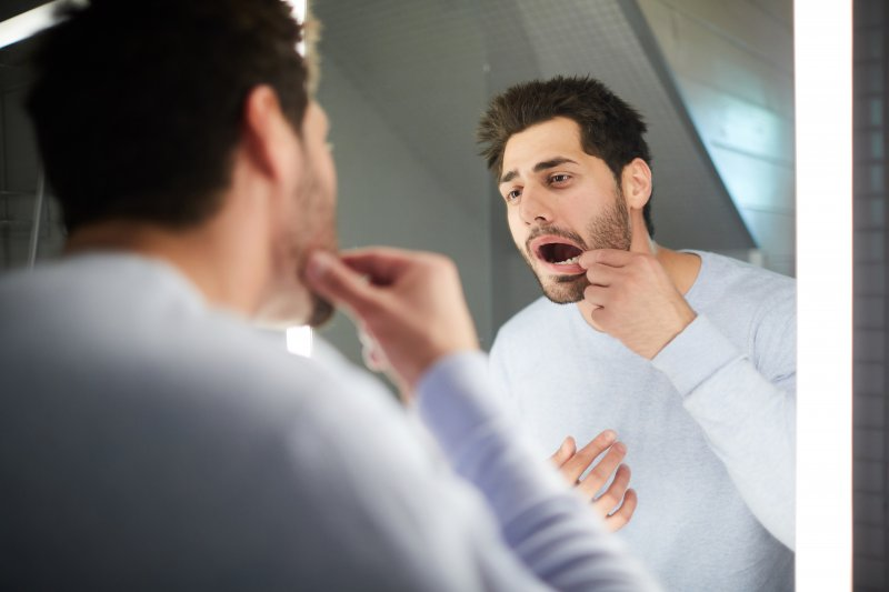 Man checking tooth in hotel mirror